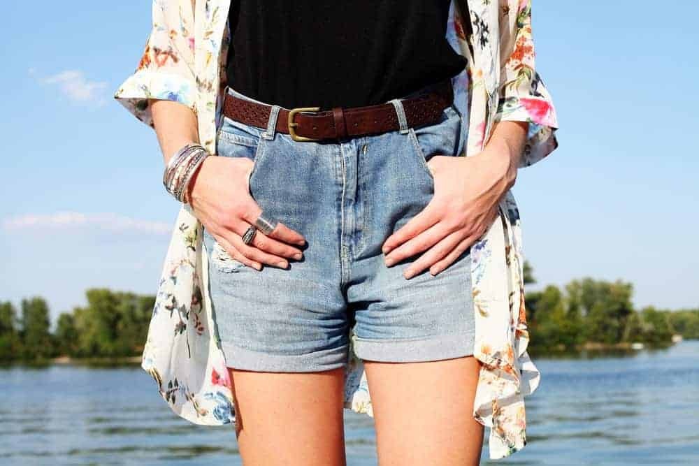 A close look at a woman wearing a pair of denim boyfriend shorts with her kimono.