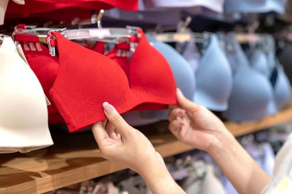 A woman browsing through bras on display.