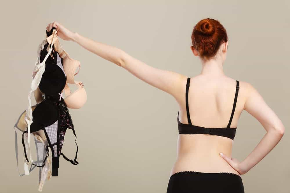 A woman holding pieces of bras.