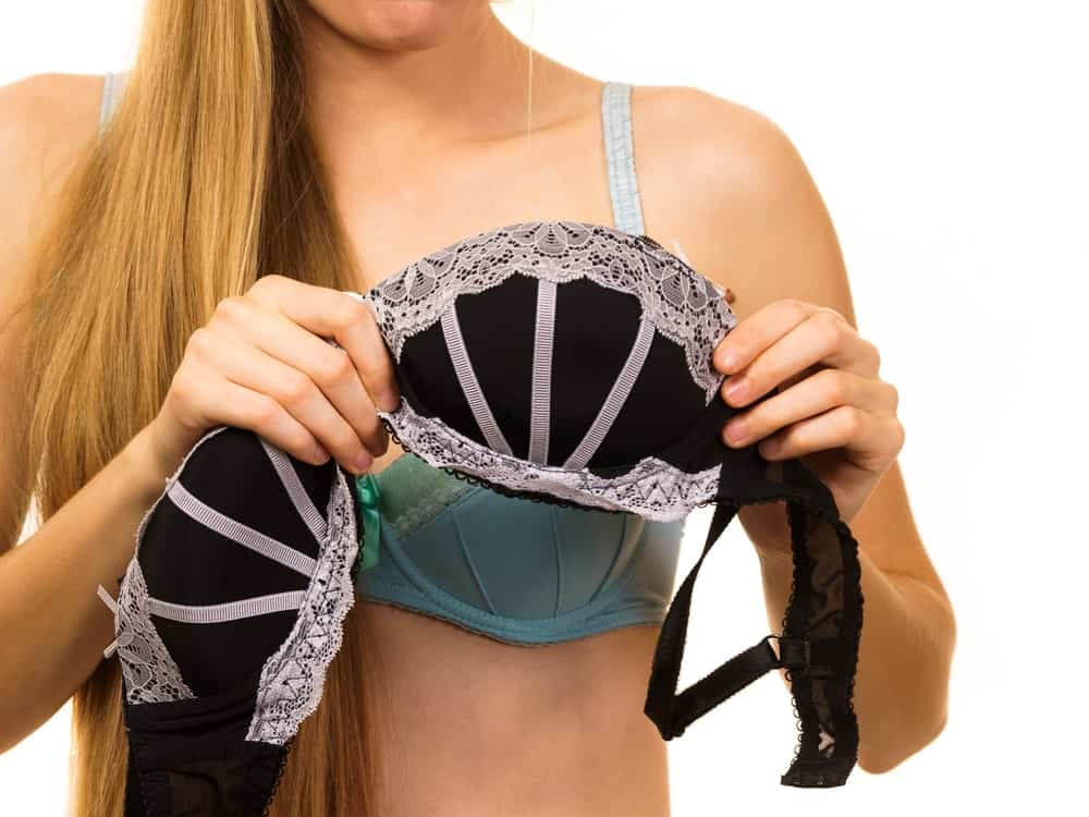 A woman holding up a piece of underwire bra with lace.