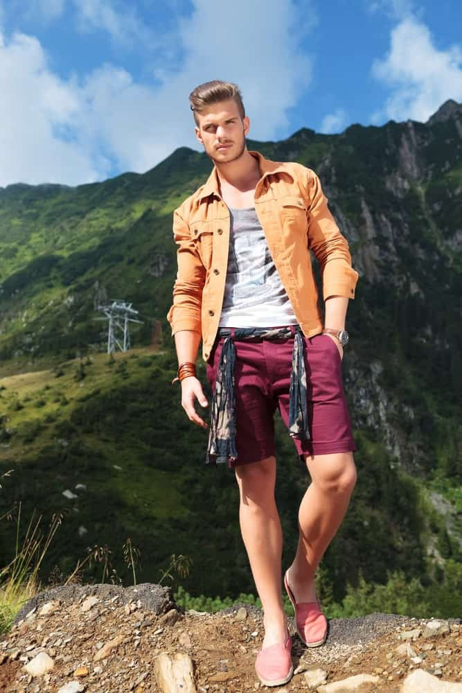 A man on a hike wearing a pair of red chino shorts.