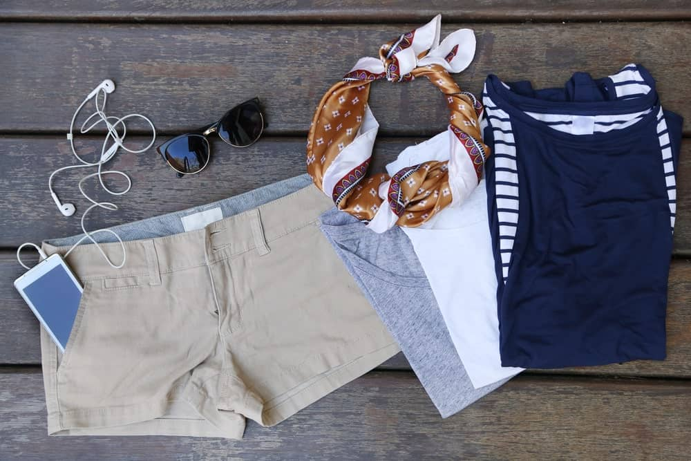 A cool outfit with shirts, a scarf and a pair of khaki shorts.