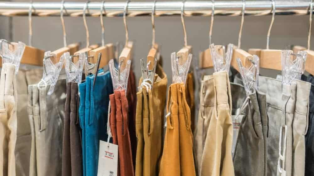 A rack of various chinos on display.