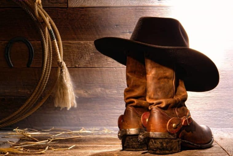 A pair of leather cowboy boots with a cowboy hat.