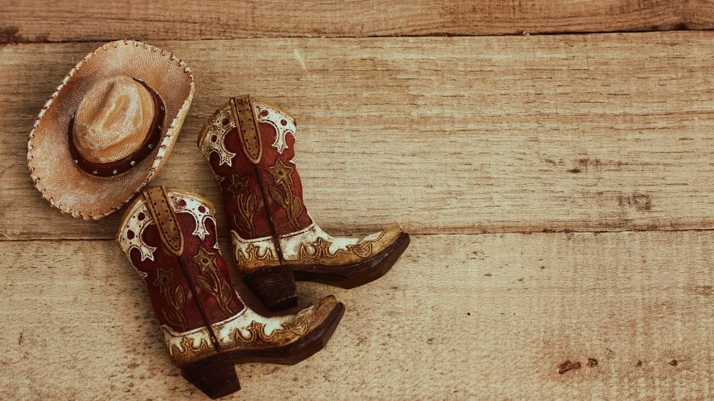 A pair of detailed cowboy boots and a straw hat.