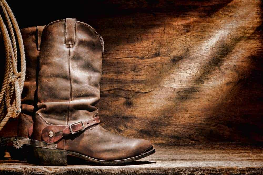 A rustic pair of brown leather roper cowboy boots.