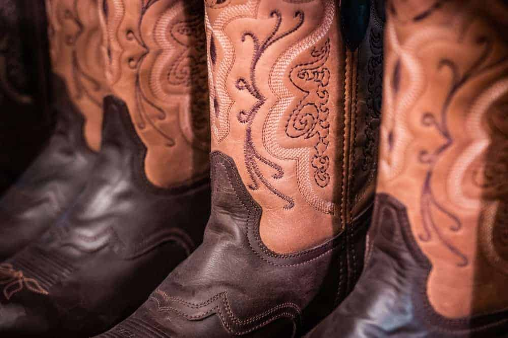 A close look at a collection of brown leather handmade cowboy boots.