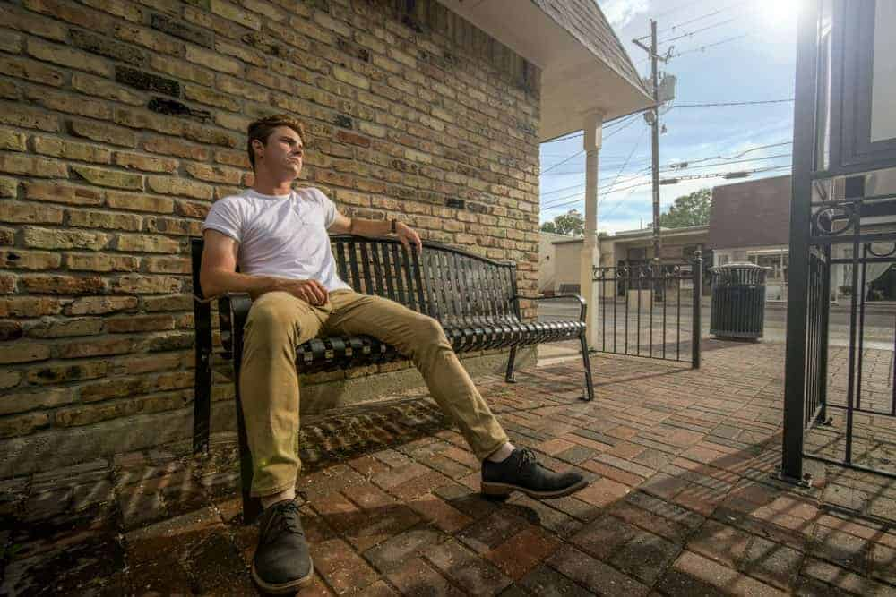 A man wearing a pair of khaki pants sitting on a bench.