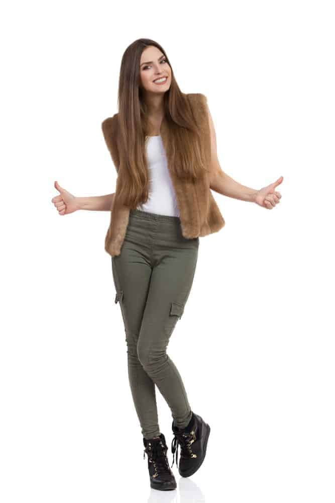 A woman wearing a pair of fitted khaki pants.