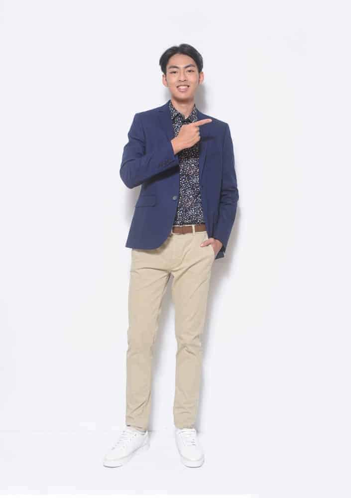 A man wearing a blazer and a pair of classic khaki pants.