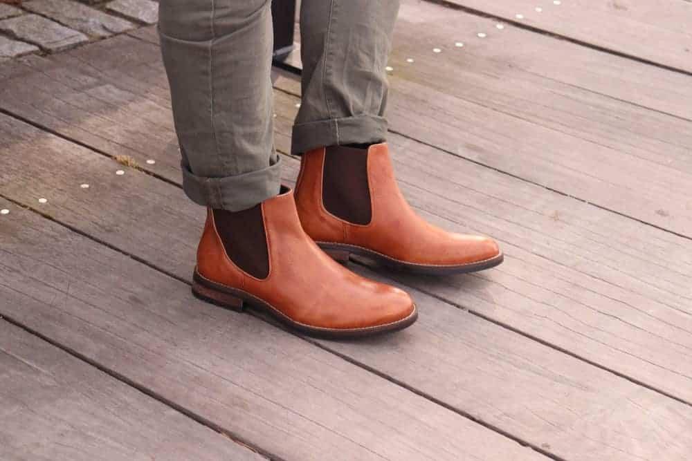 A close look at a man wearing boots and folded khaki pants.