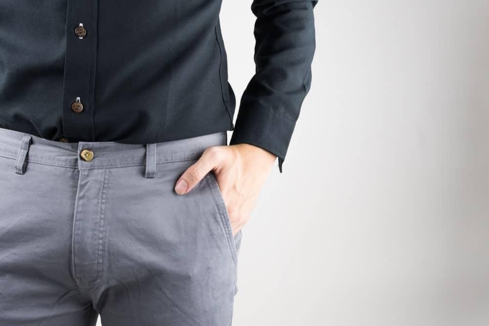 A close look at a man wearing a black button shirt and gray pants.