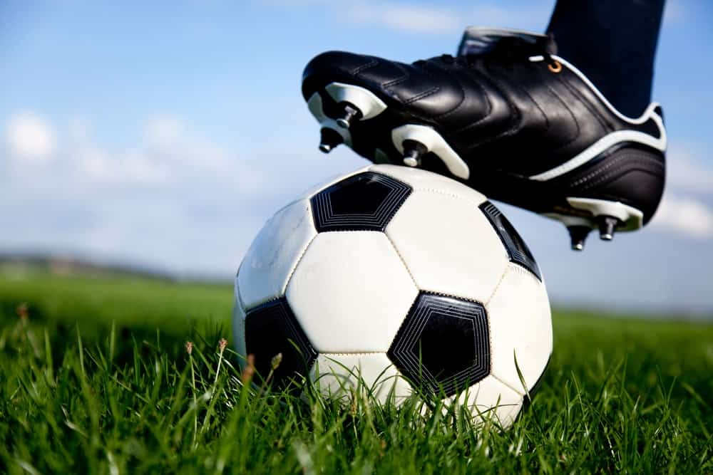 A close look at the foot of a soccer player with the shoes and the ball.