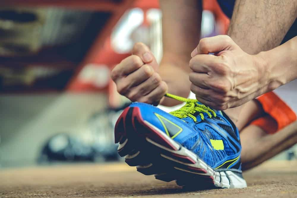 A close look at a man tying his shoes.