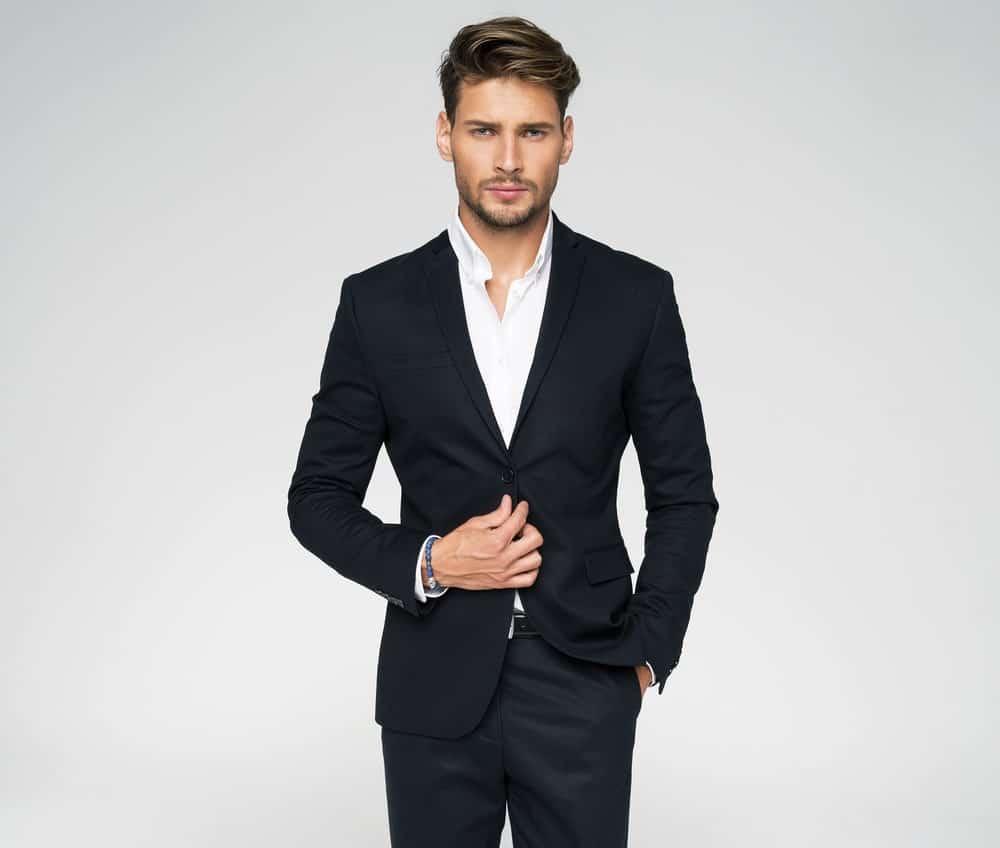 A man wearing a black slim fit suit.