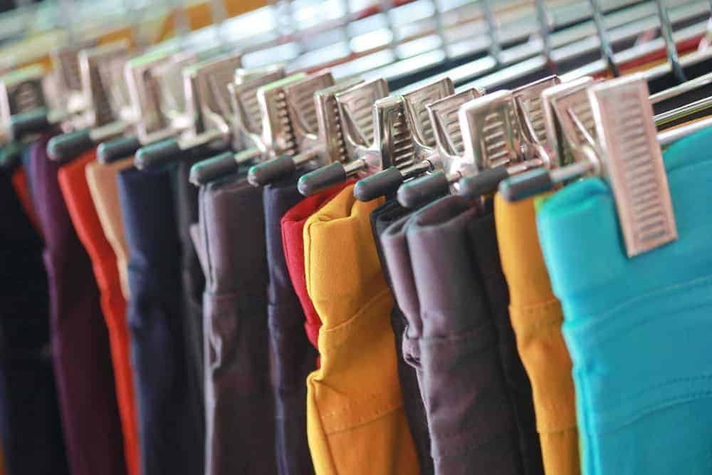 A close look at a rack of various colorful trousers.