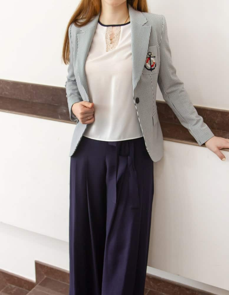 A woman wearing a blazer with her pleated pants.