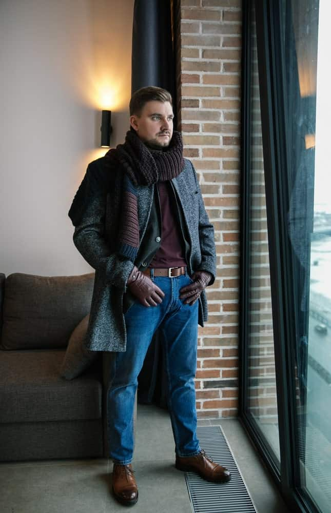 A man wearing a pair of jeans with his coat.