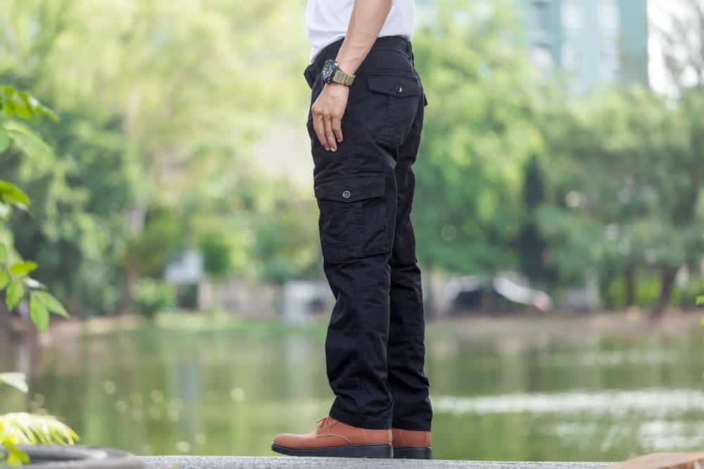 A close look at a man wearing black cargo pants.