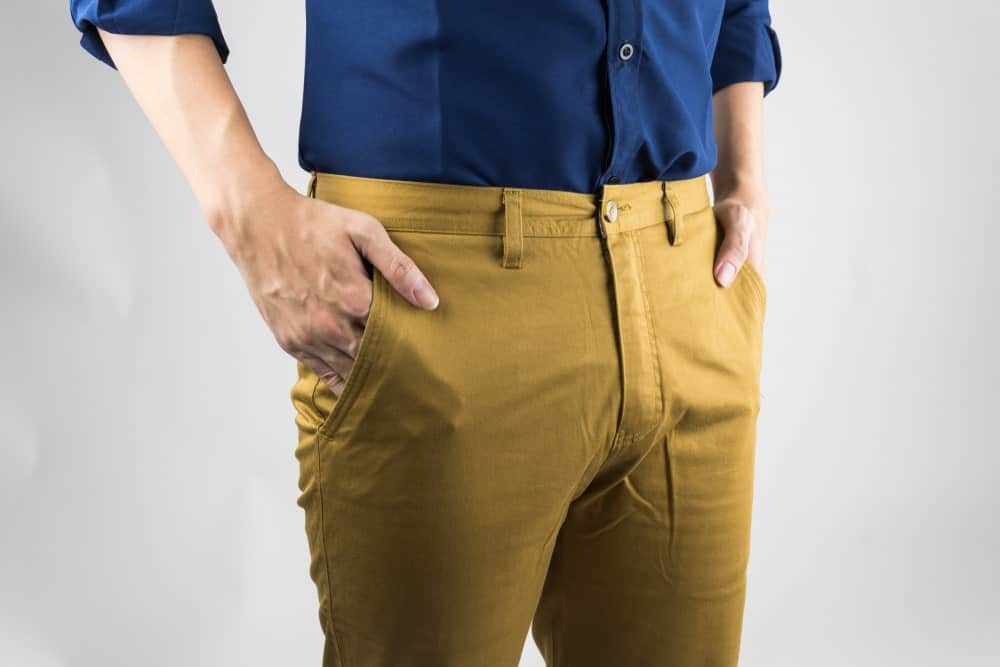 A close look at a man wearing a pair of yellow chinos.