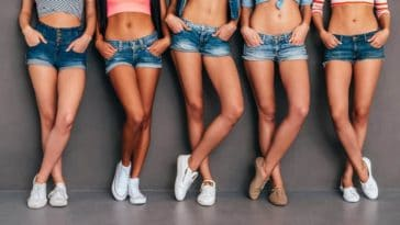 A row of women wearing cutoff jeans shorts.