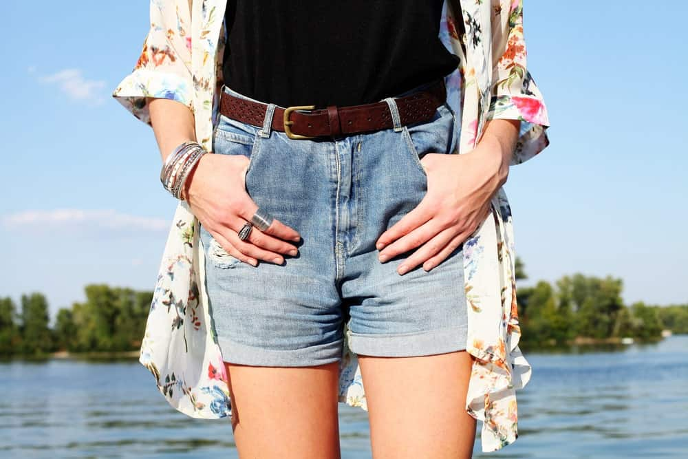 A close look at a woman wearing a pair of relaxed denim shorts.
