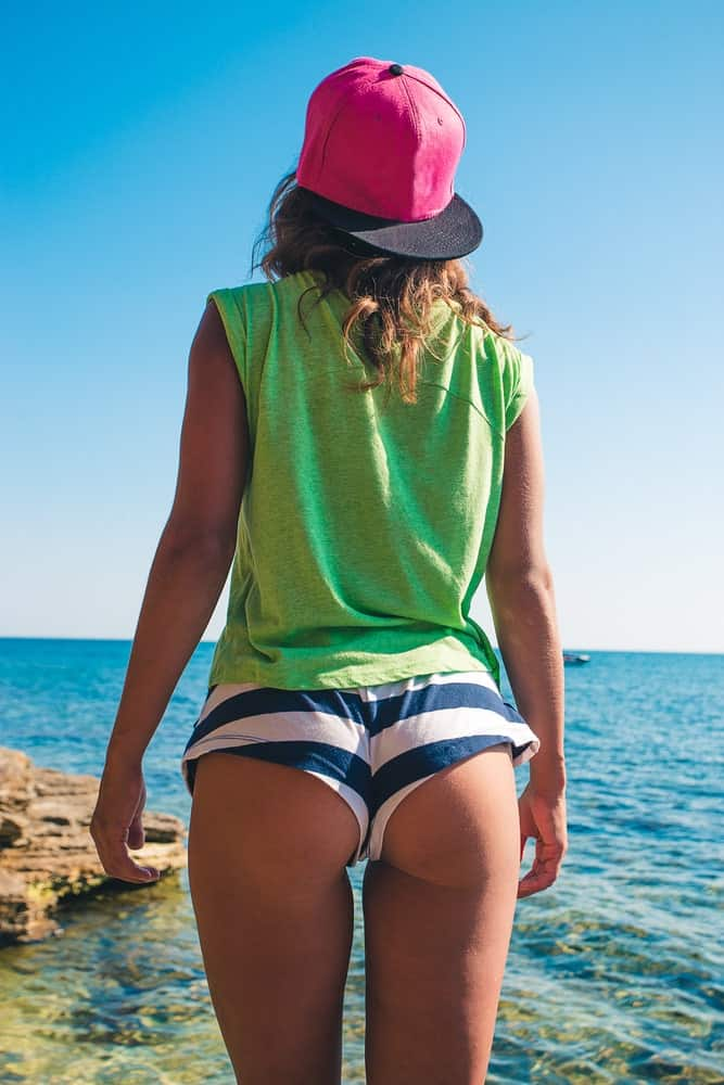 A woman wearing booty shorts at the beach.