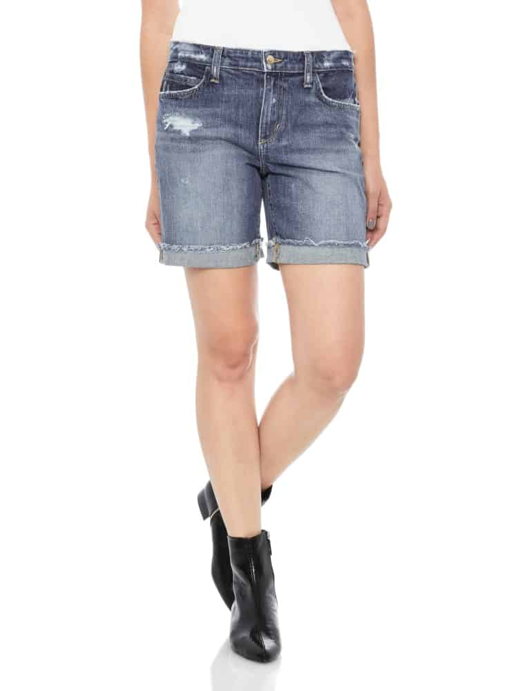 A woman wearing a pair of denim mid-length shorts.