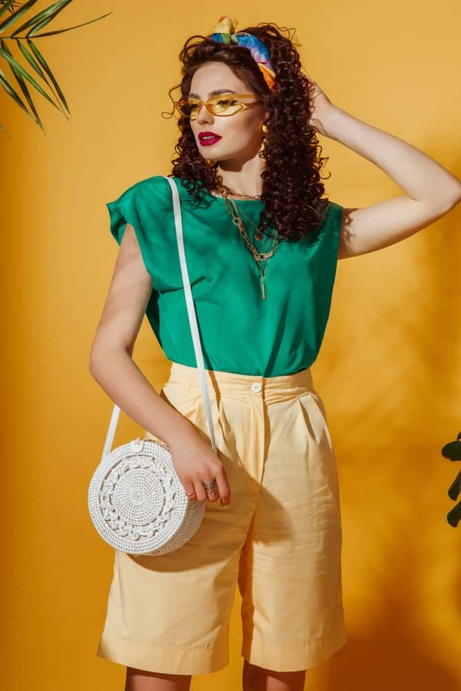 A woman with a green blouse and yellow long shorts.
