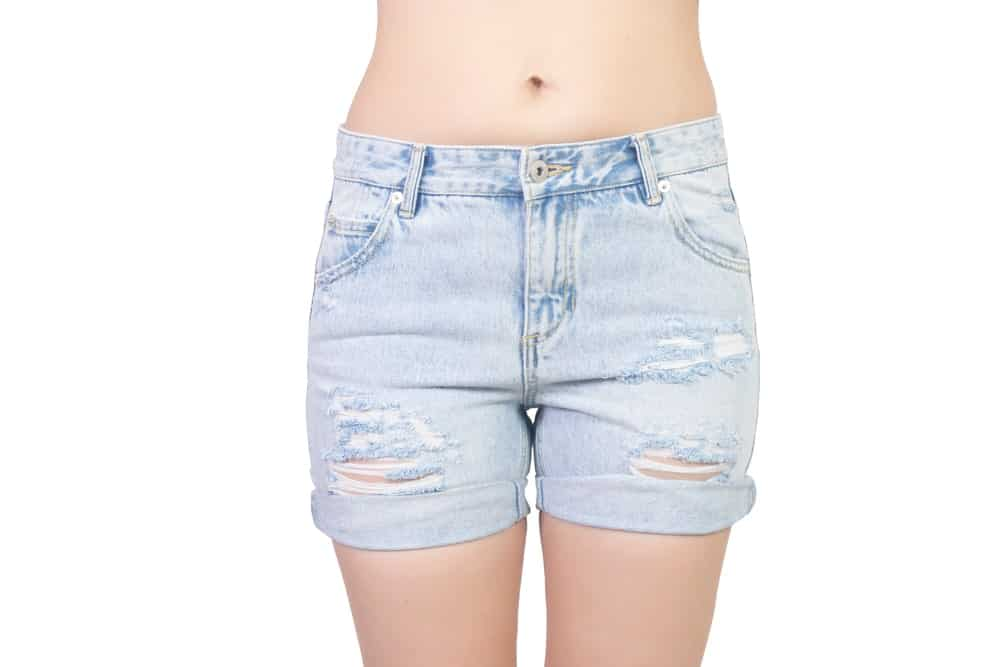 A close look at a woman wearing a pair of ripped denim shorts.