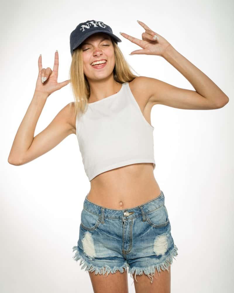 A woman wearing a pair of distressed cutoff denim shorts.