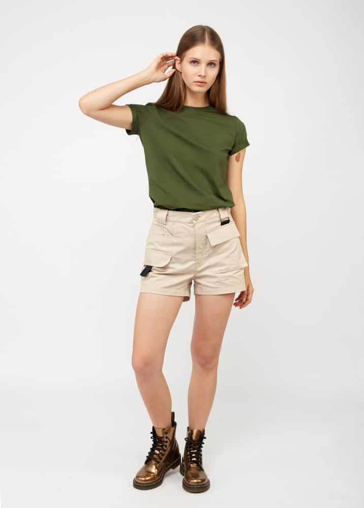 A woman wearing a pair of khaki shorts with boots.
