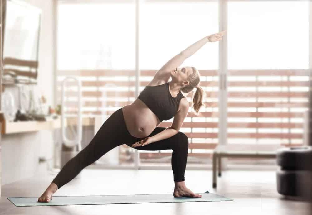 A pregnant woman wearing maternity yoga pants at home.