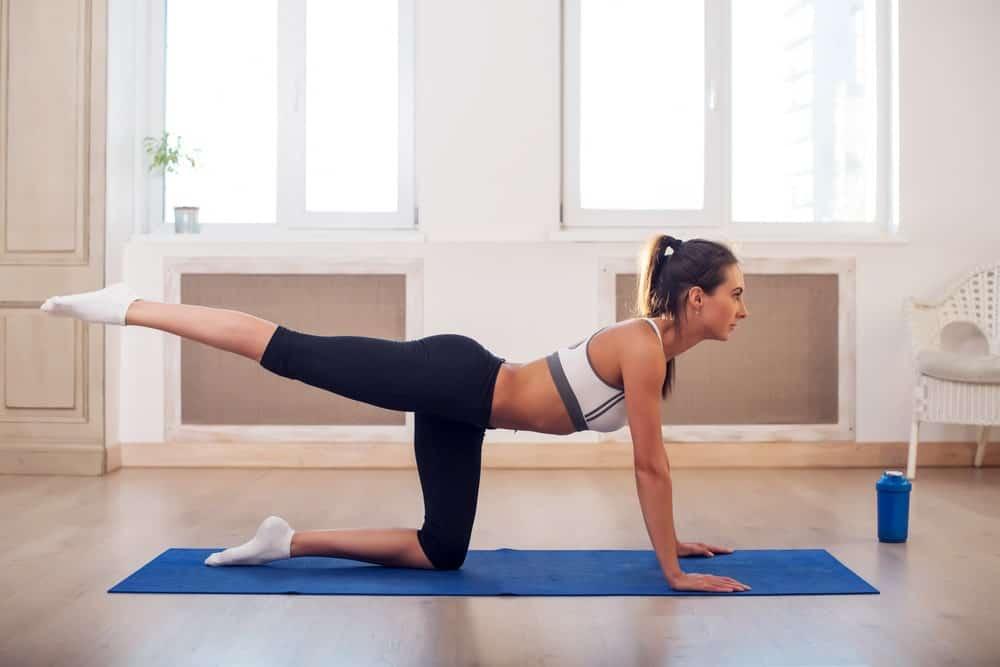 A woman wearing yoga capri pants while doing yoga positions.