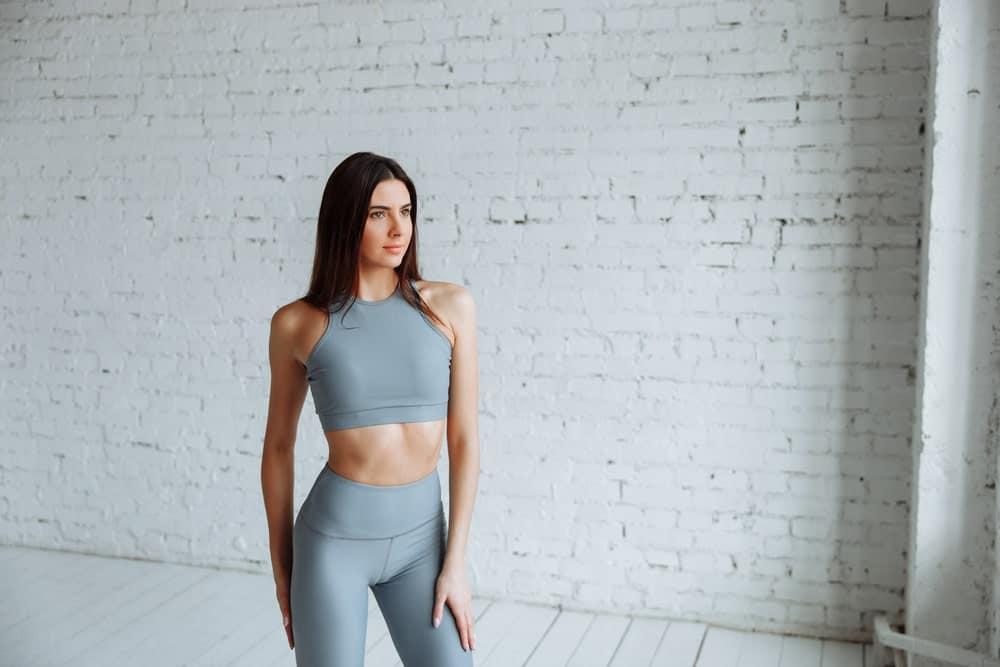 A woman wearing high waist yoga pants at a studio.