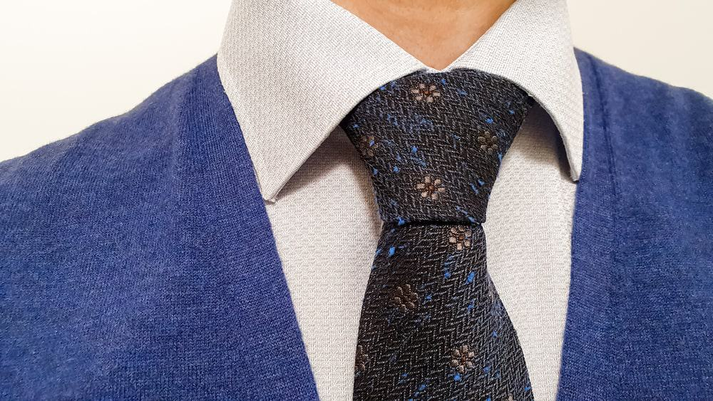 Marine blue tie with brown floral pattern in a half-Windsor knot.