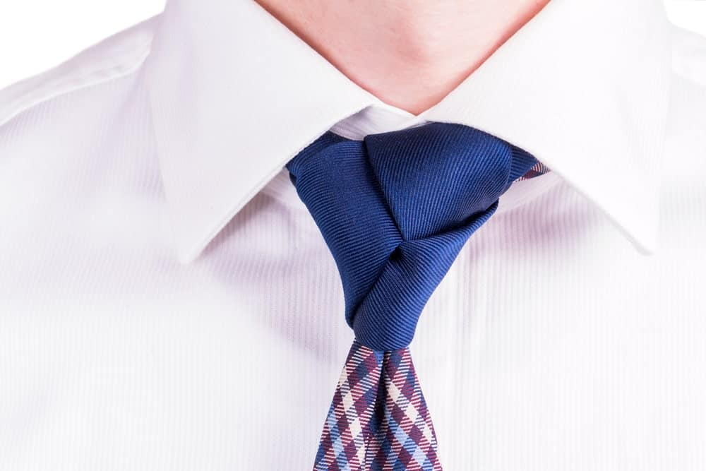 Blue necktie with Trinity tie knot on a white long sleeve.
