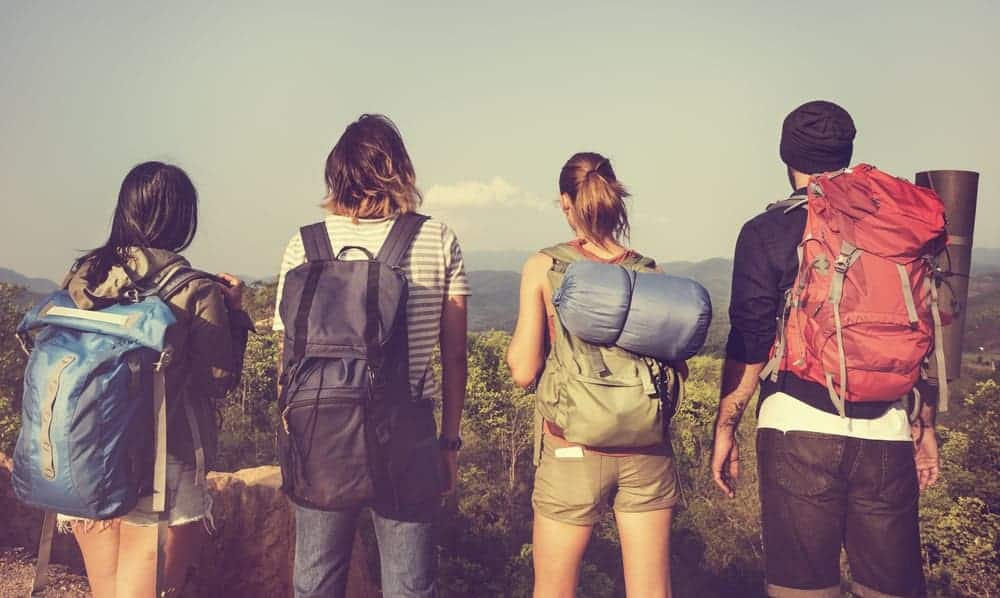 A group of friends carrying different backpacks.