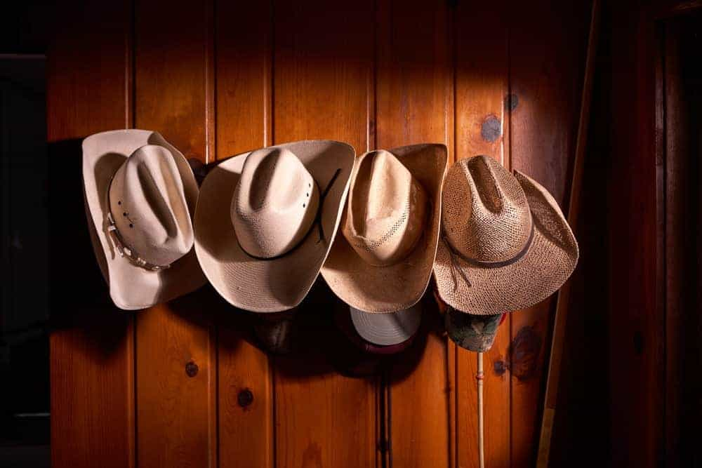 A close look with a variety of cowboy hats hanging on the wooden wall.