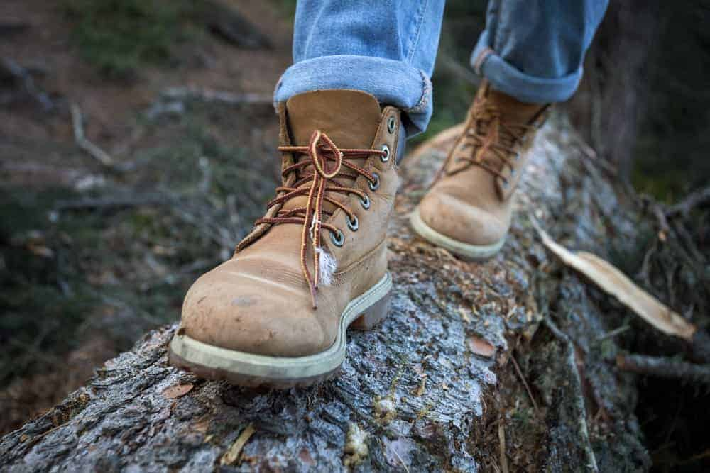 A man on a hike wearing a pair of brown hiking shoes.