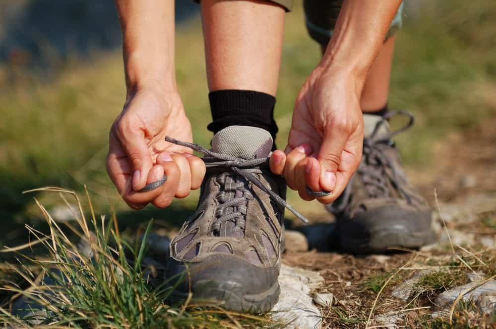 A woman lacing her day hiking boots.