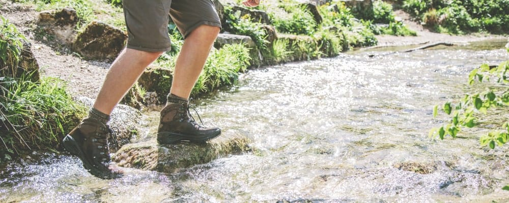 A man on a hike wearing water-proof boots.
