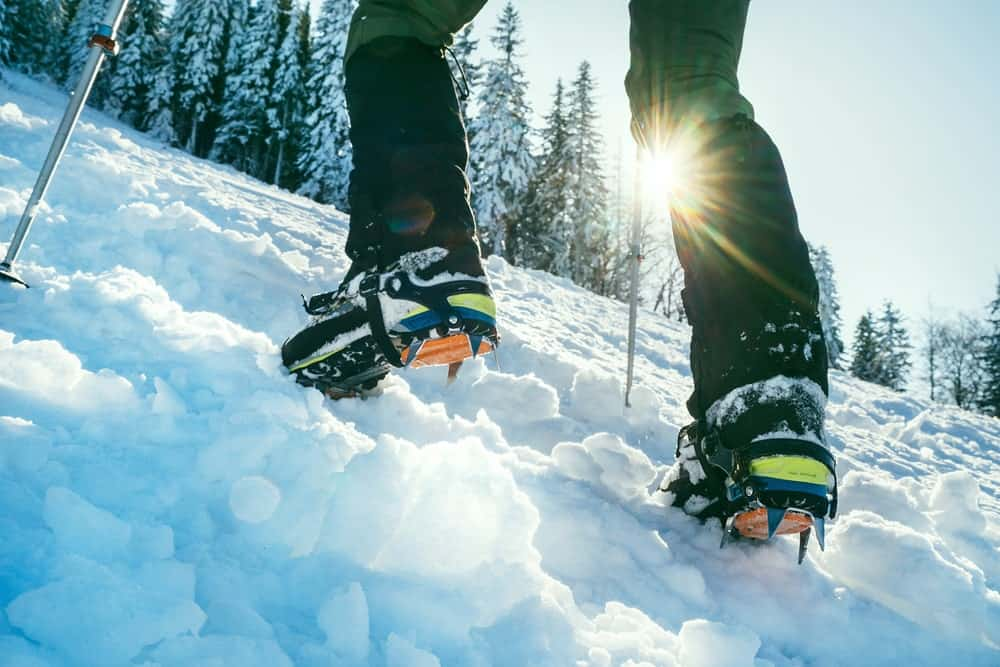 A man wearing a pair of mountaineering boots on a snowy mountain.