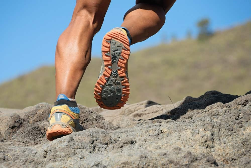 A runner wearing a pair of trail runner shoes.