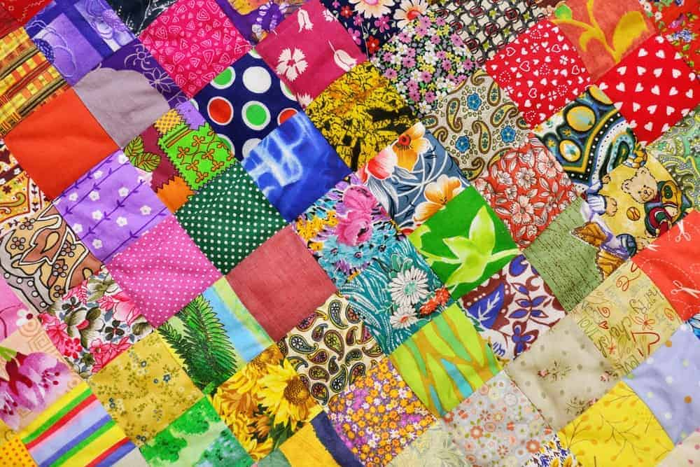 A close look at the colorful design and pattern of a one patch block quilt.
