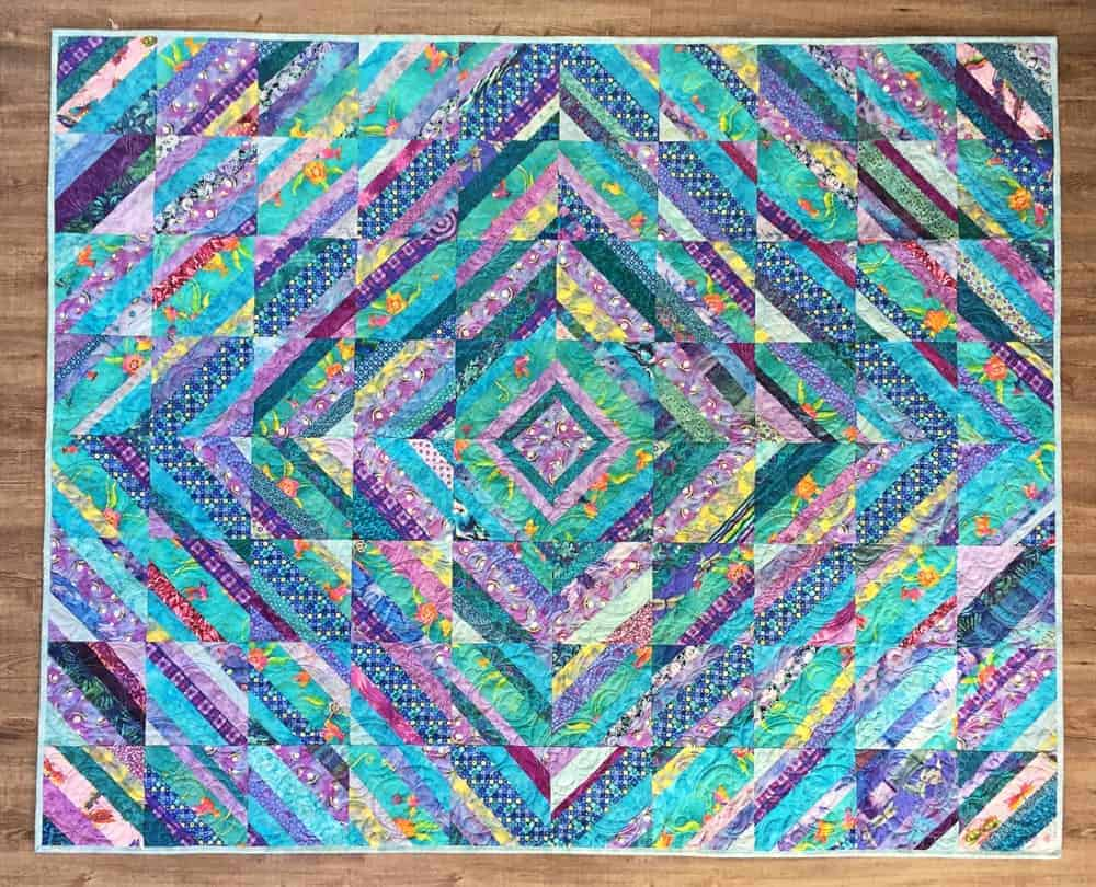 A colorful string quilt with patterns.