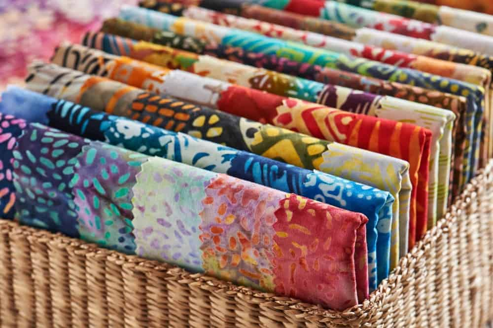 A basket of colorful quilts.