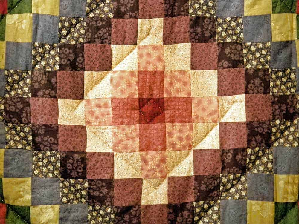 This is a close look at a colorful quilt with a diamond design.
