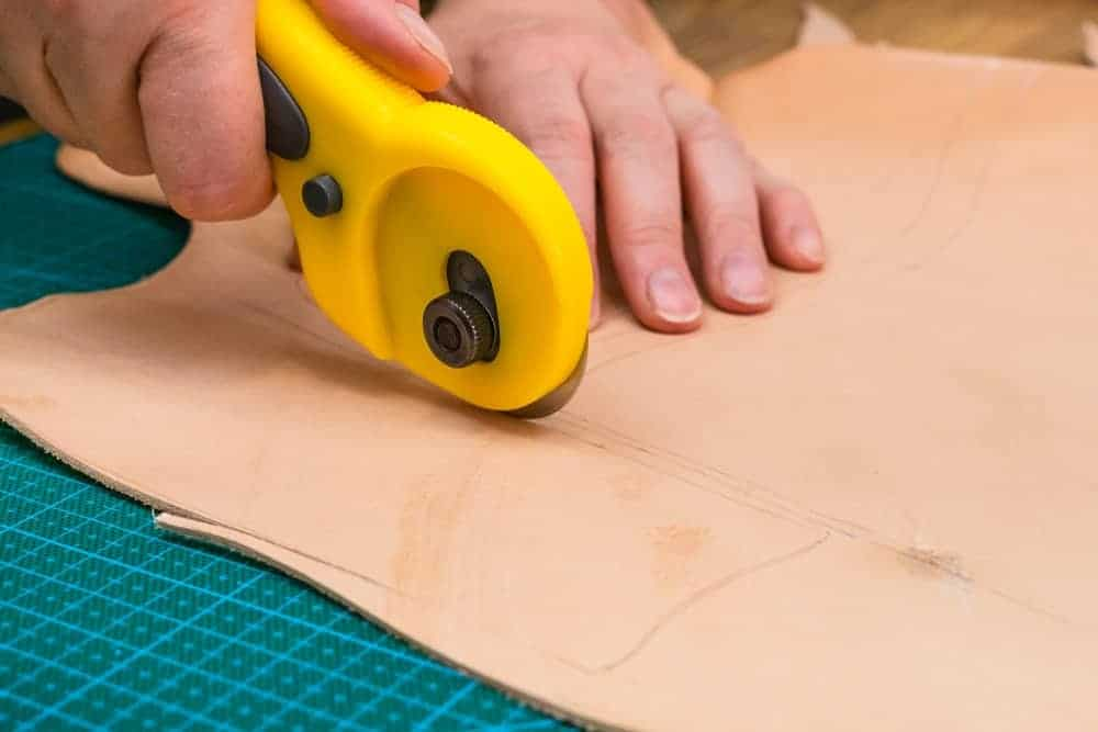 A rotary cutter being used to cut a material.
