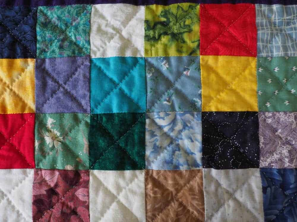 A colorful charm quilt with a checkered design.